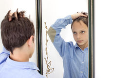 Young Boy Combing His Hair in Mirror Royalty Free Stock Image