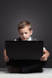 Young boy with computer. funny child looking in notebook Stock Photo