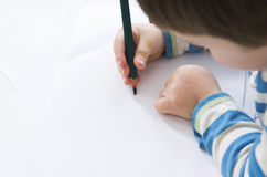 Young boy concentrates while drawing with a green pencil Royalty Free Stock Photography
