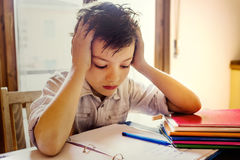 A young boy concentrating on homework. A young boy concentrating on homework at home Royalty Free Stock Photography