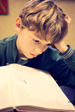 A young boy concentrating on homework. Royalty Free Stock Photo