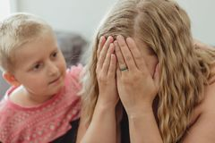 Young boy concerned for his mother and leaning into her comforting her as she cries royalty free stock images