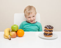 A young boy considers whether he will have a unhealthy doughnut Stock Image