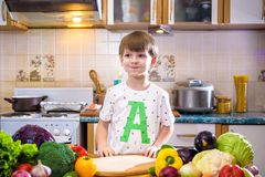 The young boy in cooking standing in the kitchen near table with Stock Images
