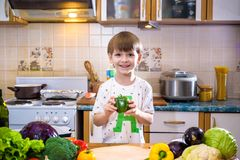 The young boy in cooking standing in the kitchen near table with Stock Photo