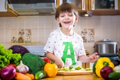 The young boy in cooking standing in the kitchen near table with Royalty Free Stock Photo