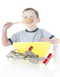 Young boy cooking and tasting Royalty Free Stock Photo