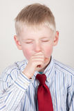 Young boy coughing. Young boy with his hand to his mouth coughing, studio background Royalty Free Stock Image