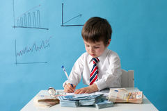 Young boy, counting money and taking notes. Isolated background Royalty Free Stock Image
