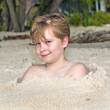 Young boy covered by fine sand Royalty Free Stock Photo