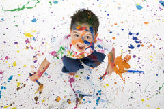Young Boy Covered in Paint Splatter. Attractive young boy covered in paint splatters having a great time stock photo