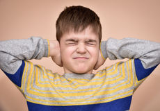 Young boy covering his ears with hands. Young boy with closed eyes covering ears with hands royalty free stock photo