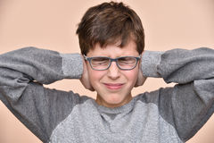 Young boy covering his ears with hands. Young boy with glasses and closed eyes covering ears with hands Royalty Free Stock Photo