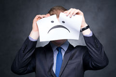 Young boy covering his face. Young boy in a suit covers his face behind piece of paper Royalty Free Stock Photography