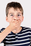 Young boy covering his mouth Royalty Free Stock Image