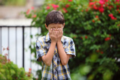 Young boy covers his eyes with hands Stock Images