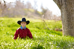 Young boy in cowboy hat. Stood in tall green grass in countryside Stock Photos