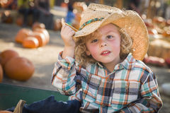 Young Boy in Cowboy Hat at Pumpkin Patch. Adorable Little Boy Wearing Cowboy Hat at Pumpkin Patch Farm Royalty Free Stock Image
