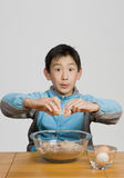 Young boy cracking egg into bowl Royalty Free Stock Photo