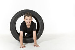 Young boy is crawling through a tire Stock Image