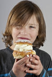 Young boy with a cream bun with almond paste. Young boy holding a cream bun with almond paste in front of his happy face Royalty Free Stock Photos