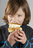 Young boy with a cream bun with almond paste. Young boy enjoying a cream bun with almond paste Royalty Free Stock Photo