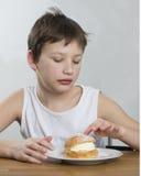 Young boy with cream bun Stock Photos