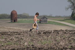 Young boy crosses field carrying straw hat stock photography