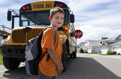 Young boy crossing in front of yellow school bus stock photo
