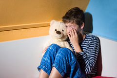 Young boy crying. A young boy is crying on his bed in his bedroom Stock Image