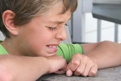Young boy crying at a table. Boy with folded arms crying at a table Royalty Free Stock Photo