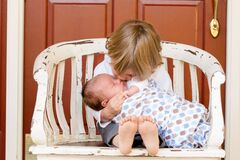 Young boy cuddling baby brother Stock Image