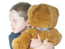 Young boy cuddling bear Stock Image