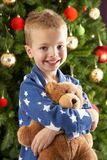 Young Boy Cuddling Teddy Bear In Front Of Tree Royalty Free Stock Photography