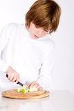 Young boy cuts the apple Stock Image