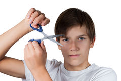 Young boy cutting his hair with scissors. This image has attached release Royalty Free Stock Image