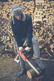 Young boy prepares firewood with chainsaw Royalty Free Stock Images