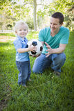 Young Boy and Dad Playing with Soccer Ball in Park Royalty Free Stock Photography