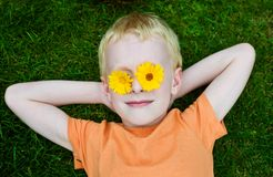 Young boy with daisies on eyes. Laying on the grass Stock Image