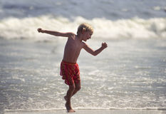 Young boy dancing at shoreline Royalty Free Stock Photos