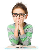 Young boy is daydreaming while reading book Royalty Free Stock Photography