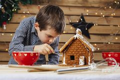 Young boy decorating gingerbread house. Photo of a young boy decorating a gingerbread house at home just before Christmas stock images