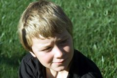 Young boy deep in thought. Young boy in the grass with a thoughtful expression on his face royalty free stock image