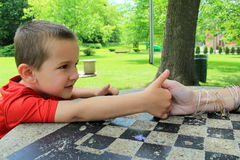 Young boy determined to beat his mom at thumb wrestling Stock Photography