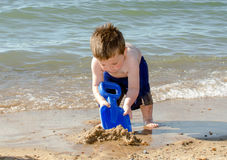 Young boy digging in the sand Stock Photo