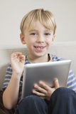Young boy with digital tablet gesturing OK Royalty Free Stock Photo