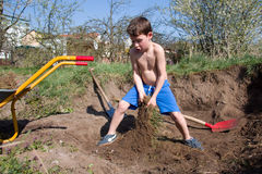 Young boy digs a hole Royalty Free Stock Images