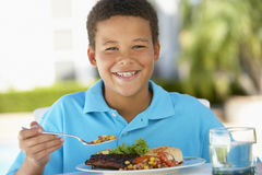 Young Boy Dining Al Fresco Royalty Free Stock Photography