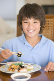 Young boy in dining room eating chinese food. Smiling Royalty Free Stock Photos