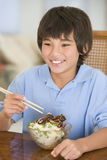 Young boy in dining room eating chinese food. Smiling Stock Image